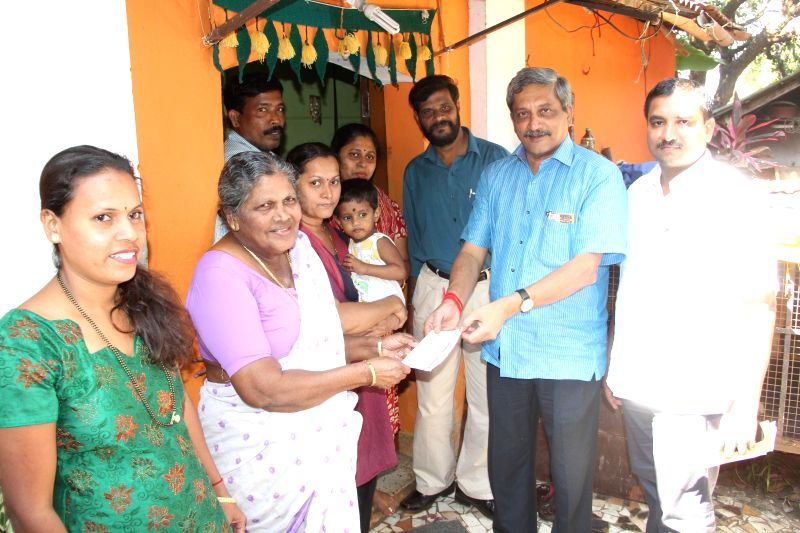 Union Defence Minister Manohar Parrikar hands over BJP membership card to a family in Ribandar, Goa on Nov 30, 2014.
