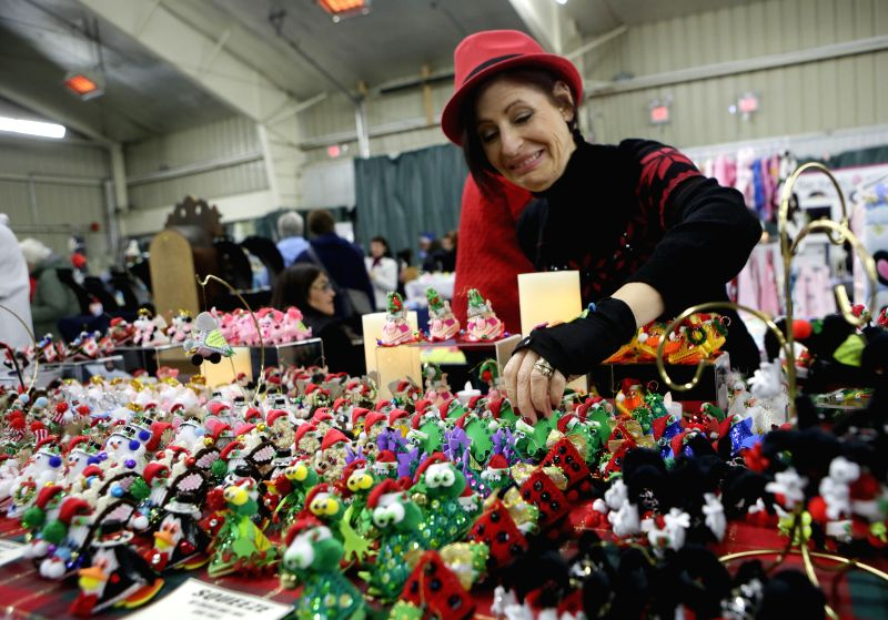 Richmond (Canada): A vendor displays her self made hand crafts at the Christmas craft fair in Richmond, Canada, Nov. 29, 2014. The Christmas craft fair showcases over 160 tables of crafts, baked, ...