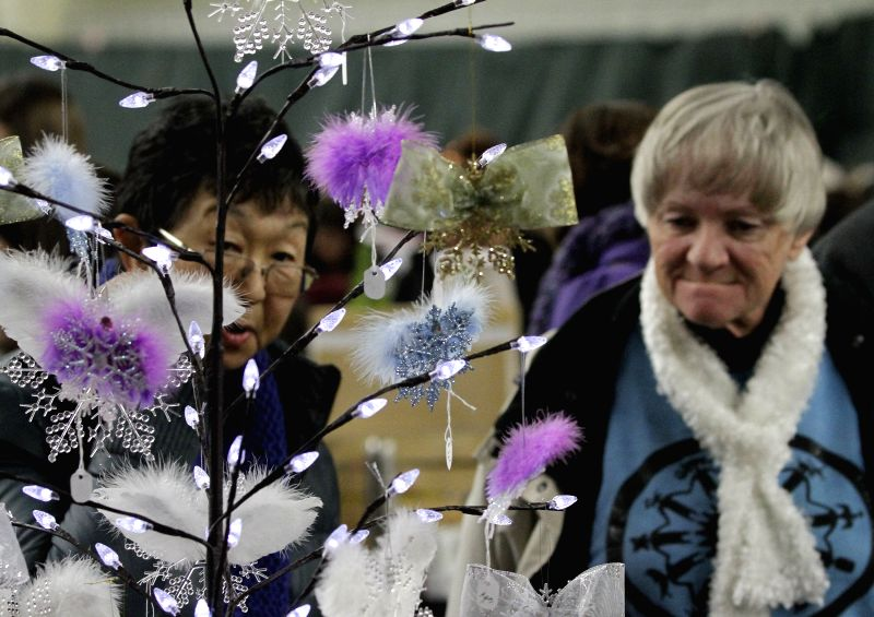 Richmond (Canada): Residents look for some hand crafts from a vendor at the Christmas craft fair in Richmond, Canada, Nov. 29, 2014. The Christmas craft fair showcases over 160 tables of crafts, ...