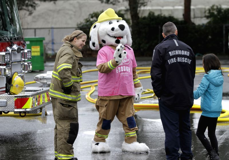 A mascot of fire hall wearing pink shirt to support anti-bullying greets a schoolgirl at a fire hall in Richmond, Canada, Feb. 25, 2015. People from different ...