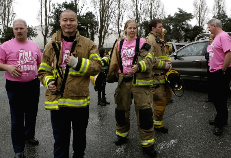 Firefighters put on pink shirts to support anti-bullying at a fire hall in Richmond, Canada, Feb. 25, 2015. People from different organizations and schools across ...