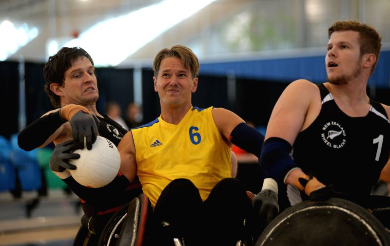 Tobias Sandberg (C) of Sweden vies with Dan Buckingham (L) of New Zealand during their match at 2014 Canada Cup International Wheelchair Rugby Tournament in ...