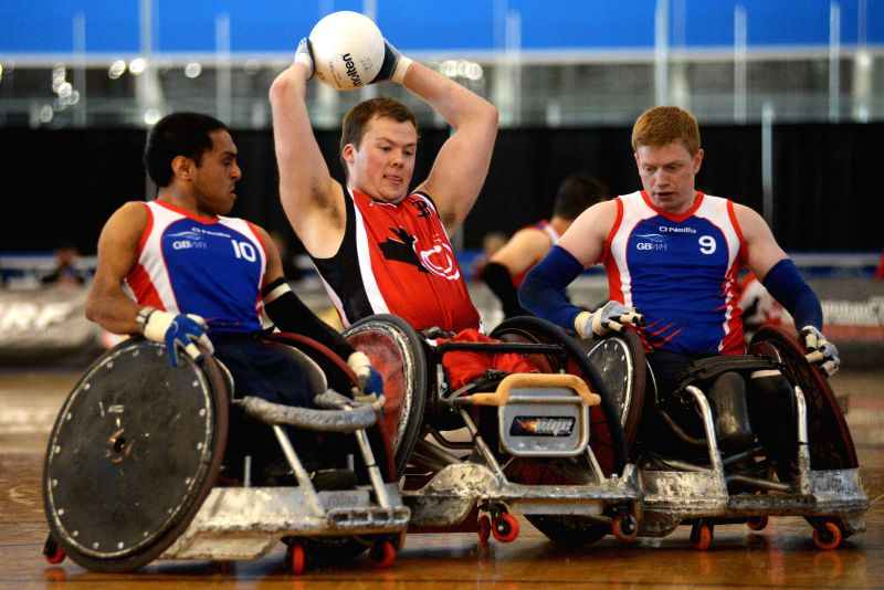 Zak Madell (C) of Canada vies with James Roberts (R) and Ayaz Bhuta of Britain during their match at 2014 Canada Cup International Wheelchair Rugby Tournament in ...