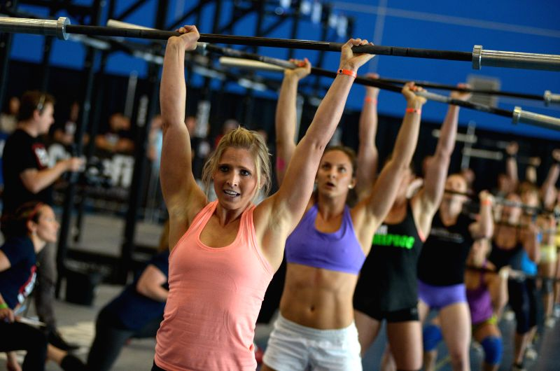 Whitney Darchuk (L) of Canada competes during opening day of 2014 CrossFit Games Canada on May 9, 2014 in Richmond, BC, Canada. The CrossFit Games are ...
