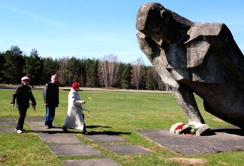 People place flowers at the Salaspils concentration camp site in Riga, Latvia on April 11, 2014. Latvian people held a commemoration  here to mourn the victims ...