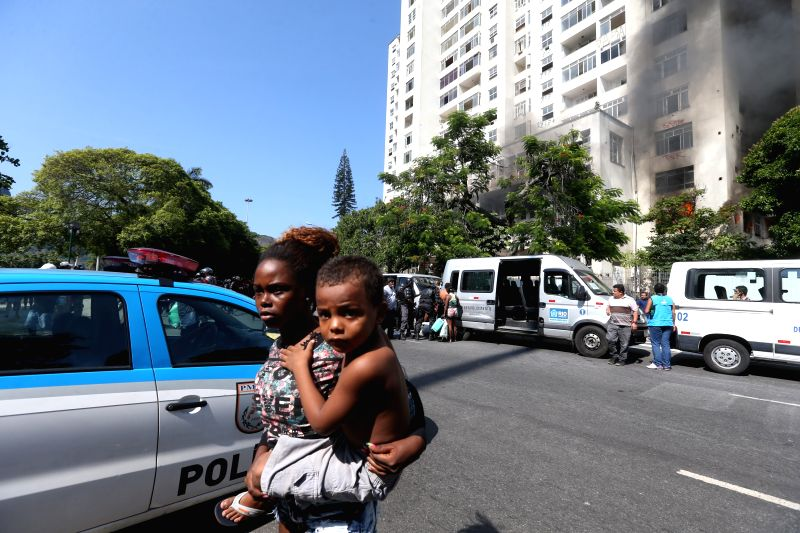 A women carries her son while being evicted from a building planned to be used as a luxury hotel in Rio de Janeiro, Brazil, on April 14, 2015. According to ...