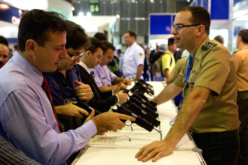 Visitors check the exhibited guns at the 2015 Latin America Aerospace and Defence international exhibition (LAAD) in Rio de Janeiro, Brazil, April 14, 2015. ...