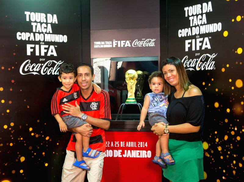 Visitors pose with the displayed FIFA World Cup Trophy in Rio de Janeiro, Brazil, April 22, 2014. The FIFA World Cup Trophy arrived in Rio de Janeiro on ...
