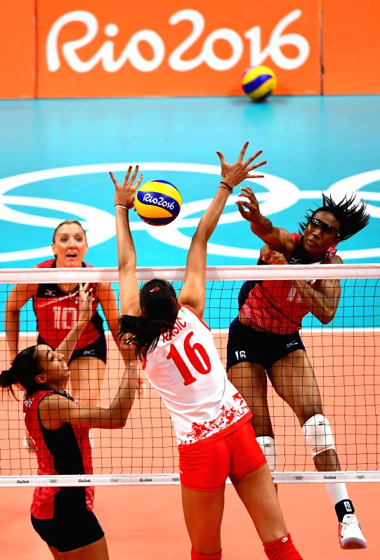 RIO DE JANEIRO, Aug. 10, 2016 - Foluke Akinradewo (R) of the Unites States of America spikes the ball against Serbia during a women's preliminary match of volleyball at the 2016 Rio Olympic Games in ...