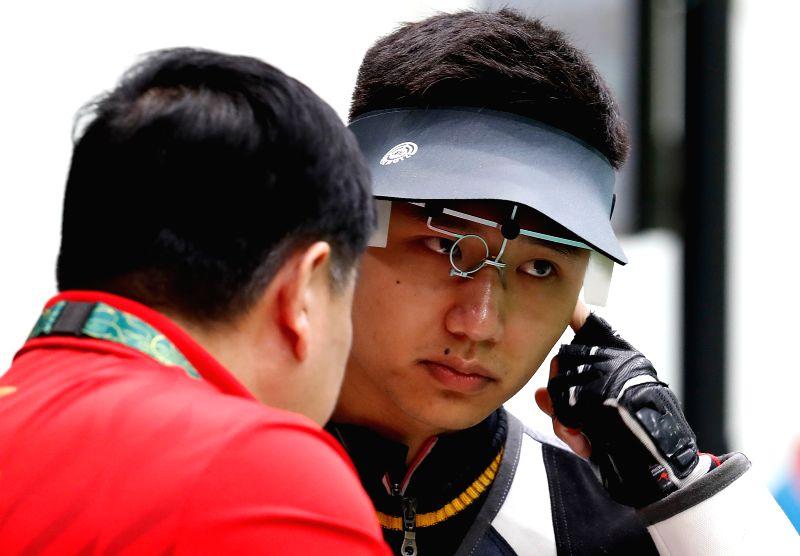 RIO DE JANEIRO, Aug. 8, 2016 - Yang Haoran (R) of China talks with coach Wang Yifu during the men's 10m Air Rifle Qualification of Shooting in Rio de Janeiro, Brazil, on Aug. 8, 2016.  Yang Haoran ...