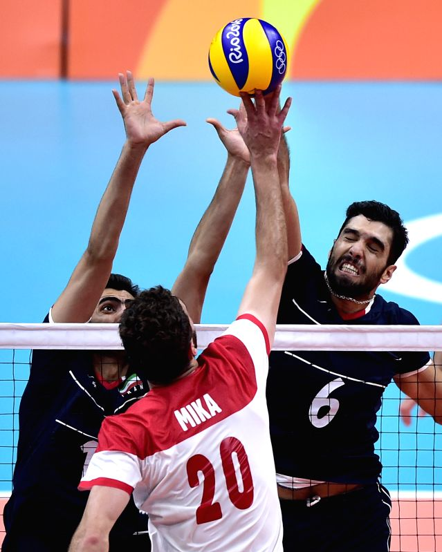 RIO DE JANEIRO, Aug. 9, 2016 - Iran's Seyed Mohammad Mousavi Eraghi (1st, R) blocks the ball against Poland's Mateusz Mika during a men's preliminary match of volleyball at the 2016 Rio Olympic Games ...