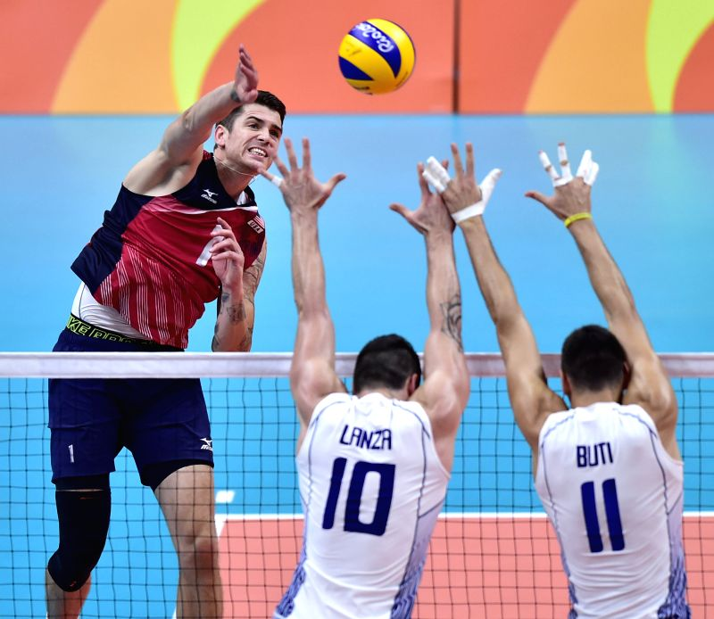 RIO DE JANEIRO, Aug. 9, 2016 - Matthew Anderson (L) from the United States of America smashes the ball against Italy during the men's volleyball preliminary match at the 2016 Rio Olympic Games in Rio ...