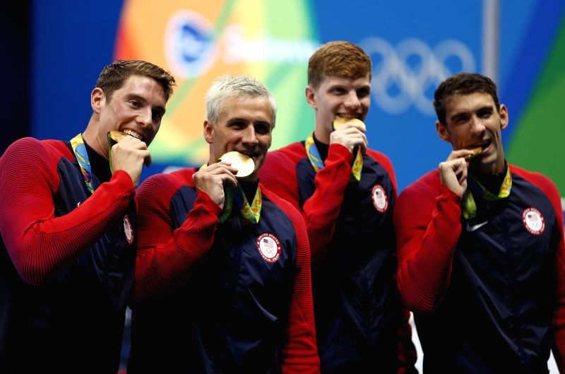 RIO DE JANEIRO, Aug. 9, 2016 - Swimmers of the United States of America bite their medals during the awarding ceremony for men?s 4x200m freestyle relay final of swimming at the 2016 Rio Olympic Games ...