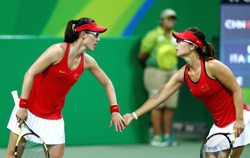 RIO DE JANEIRO, Aug. 9, 2016 - Xu yifan (R) and Zheng Saisai react during a women's doubles second round match of tennis agaisnt Italy's Sara Errani and Roberta Vinci at the 2016 Rio Olympic Games in ...
