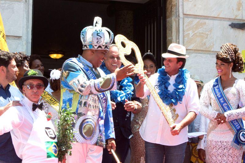 """Eduardo Paes (2nd R), mayor of the city of Rio de Janeiro, hands over the ceremonial key of Rio de Janeiro to  """"King Momo"""" Wilson Neto (2nd L) ..."""