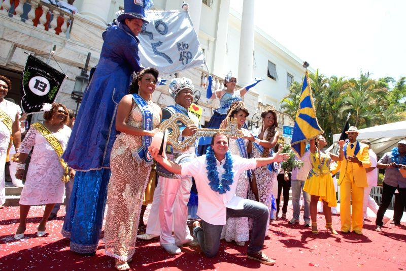 "Eduardo Paes (front), mayor of the city of Rio de Janeiro, poses for a photo after handing over the ceremonial key of Rio de Janeiro to ""King Momo"