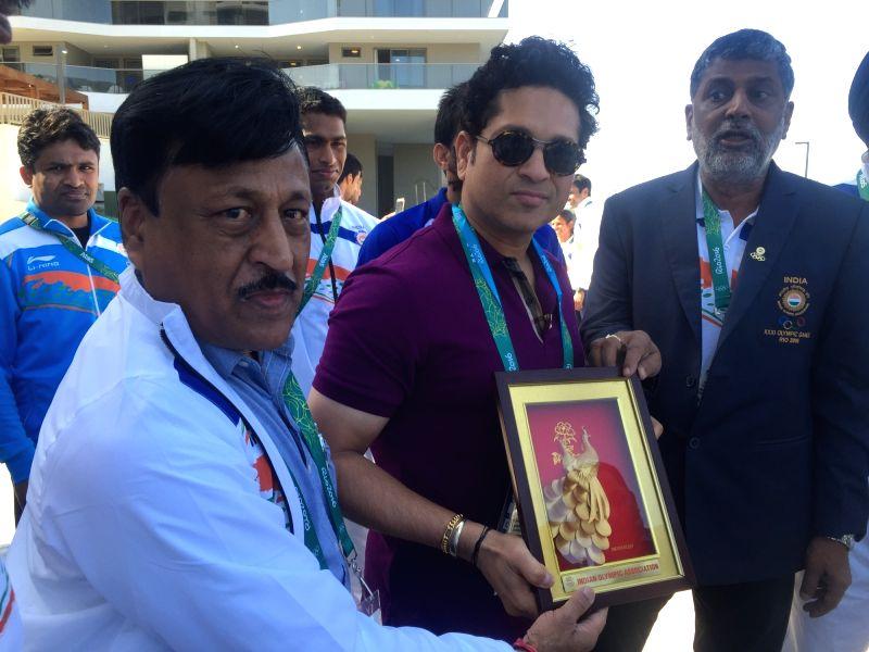Rio De Janeiro: Former Indian cricketer Sachin Tendulkar being presented memento by Rakesh Gupta, Chef de Mission, Indian Olympic Team at the Games Village in Rio de Janeiro on Aug. 6, 2016. - Sachin Tendulkar and Rakesh Gupta