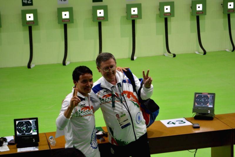 Rio De Janeiro: Indian shooter Jitu Rai with his coach after qualifying for 10m Air Pistol final in Rio de Janeiro on Aug. 6, 2016. - Jitu Rai