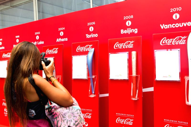A woman takes photo for the exhibited torches of the previous Olympic Games after a press conference providing the preliminary information on Olympic torch ..