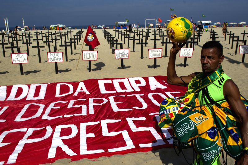 A vendor walks past crosses that are placed as part of a protest launched by the Group of Comissao de Moradores do Horto in order to call for people's ...