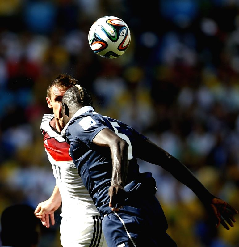 Germany's Thomas Muller (L) competes for a header with France's Mamadou Sakho during a quarter-finals match between France and Germany of 2014 FIFA World Cup .
