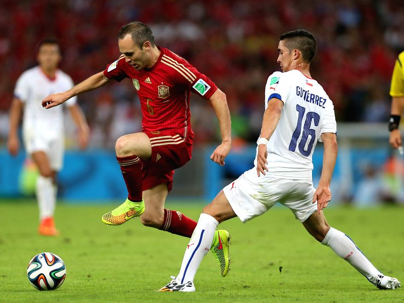 Spain's Andres Iniesta (L) vies with Chile's Felipe Gutierrez during a Group B match between Spain and Chile of 2014 FIFA World Cup at the Estadio do ...
