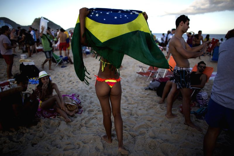 A woman holds a Brazil's national flag at the Copacabana beach, in Rio de Janeiro, Brazil, June 22, 2014.