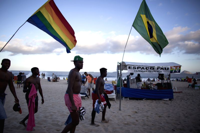 Tourists walk at the Copacabana beach where different kinds of flags are seen, in Rio de Janeiro, Brazil, June 22, 2014.