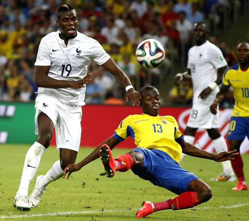 Ecuador's Enner Valencia vies with France's Paul Pogba during a Group E match between Ecuador and France of 2014 FIFA World Cup at the Estadio do Maracana ...