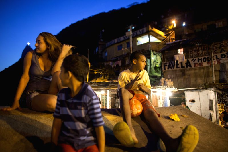 Residents sit on a terrace at Favela Santa Marta, Rio de Janeiro, Brazil, on June 26, 2014. Favela Santa Marta, founded in 1920, is one of the oldest favelas