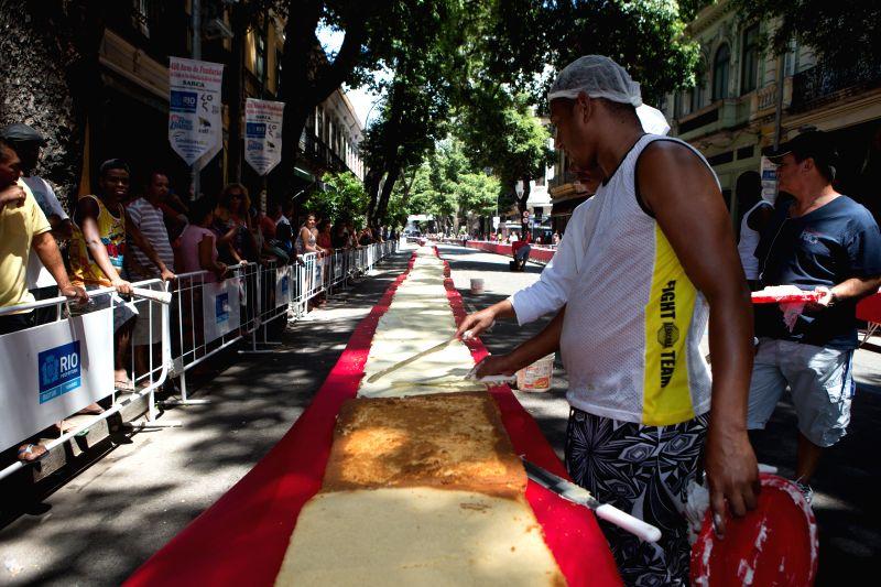 A pastry cook spreads cream onto the cake during a birthday party for the city of Rio de Janeiro, in downtown of Rio de Janeiro, Brazil, March 1, 2015. Rio ...