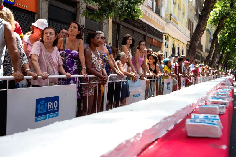 People wait beside a large cake as they attending a birthday party for the city of Rio de Janeiro, in downtown of Rio de Janeiro, Brazil, March 1, 2015. Rio ...