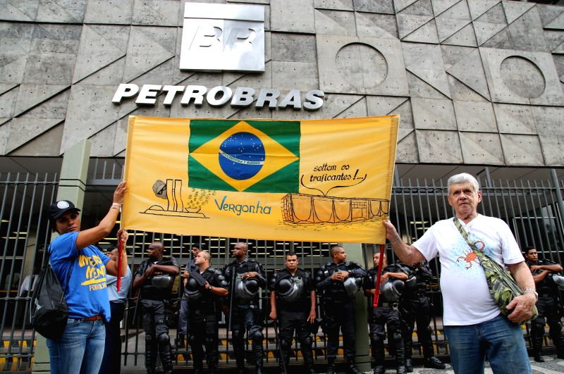People take part in a demonstration in front of the headquarters of Petrobras in Rio de Janeiro, Brazil, on March 11, 2015. The demonstrators showed their ...