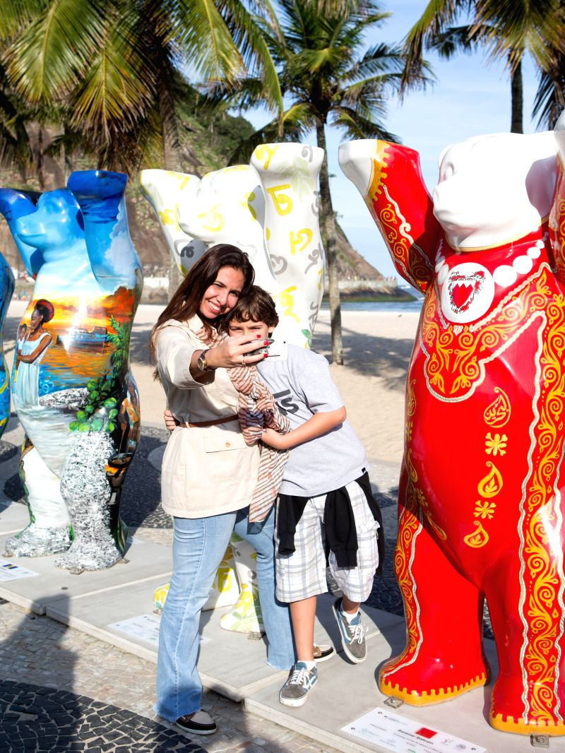 """Visitors look at the """"United Buddy Bears"""" exhibiting on the Copacabana beach in Rio de Jeneiro, Brazil, May 14, 2014. A total of 141 """"United ..."""