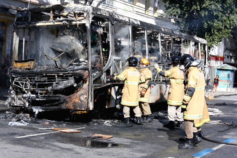 Firemen put out a fire on a bus set on by demonstrators at a protest in Rio de Janeiro, Brazil, on May 15, 2015. Demonstrators set two public buses on fire on ...