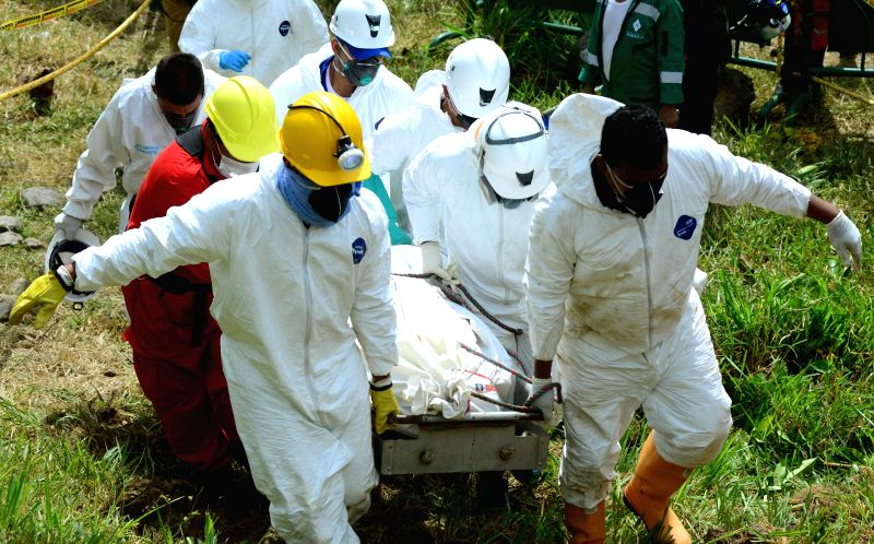 Members of the rescue services carry the body of a miner who was trapped inside a flooded gold mine in Riosucio, in Colombia, 15 May 2015. Authorities confirmed that a total of six corpses ...