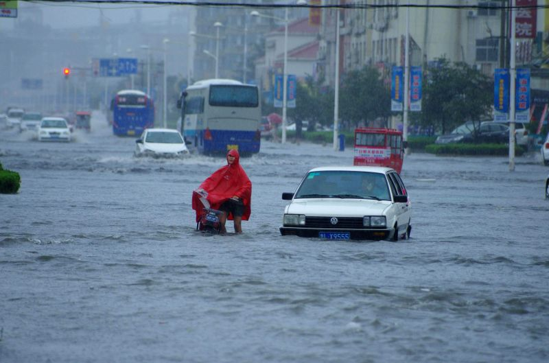 People are stranded on a waterlogged road in rainstorm in Rizhao City, east China's Shandong Province, July 25, 2014. Typhoon Matmo brought rainstorms to the ...