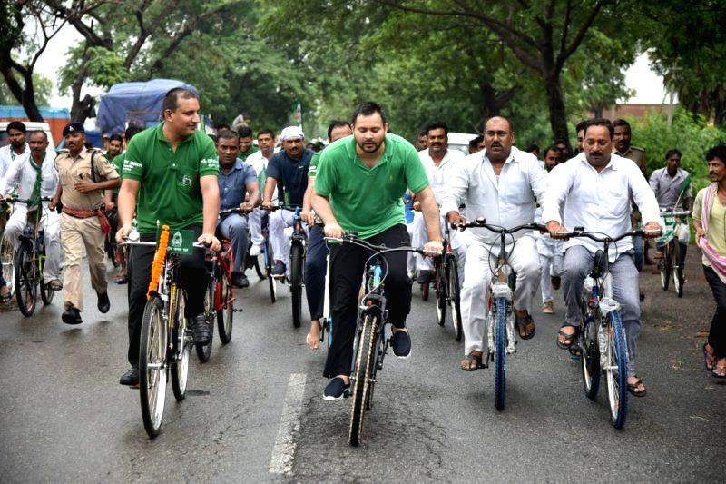 "RJD leader Tejashwi Yadav along with party workers participates in RJD's ""NDA Bhagao, Beti Bachao"" cycle rally, in Patna on July 28, 2018. - Tejashwi Yadav"