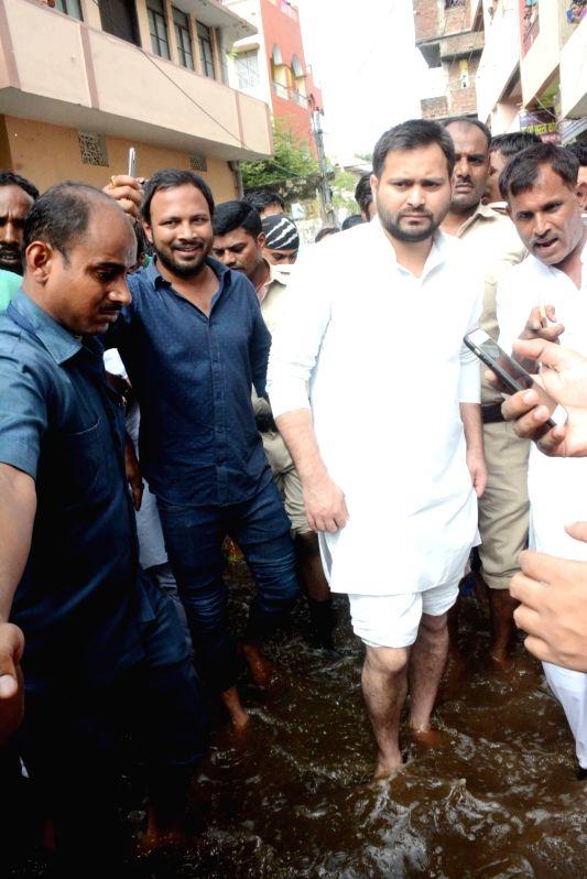 RJD leader Tejashwi Yadav takes stock of the situation of water-logging followed by heavy rains, during his visit to Ashoknagar area of Patna on Aug 1, 2018. - Tejashwi Yadav