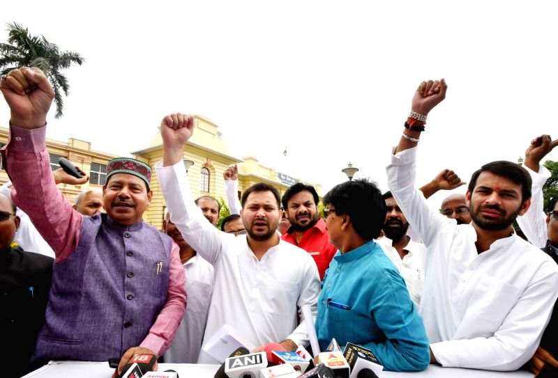 RJD leaders Tejashwi Yadav and Tej Pratap Yadav talk to the media outside Bihar Legislative Assembly, in Patna on July 24, 2018. - Tejashwi Yadav and Tej Pratap Yadav