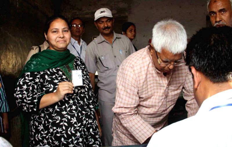 RJD supremo Lalu Prasad Yadav with his daughter Misa Bharti arrive to cast their vote during the third phase of Bihar assembly polls in Patna on Oct 28, 2015.