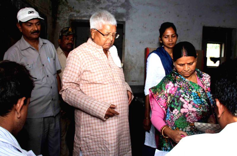 RJD supremo Lalu Prasad Yadav with his wife Rabri Devi arrive to cast their vote during the third phase of Bihar assembly polls in Patna on Oct 28, 2015.