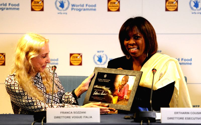 World Food Programme's Executive Director Ertharin Cousin (R) presents a souvenir to Franca Sozzani, Editor-in-Chief of Vogue Italy (L), in Rome, Italy, on May 14, ...
