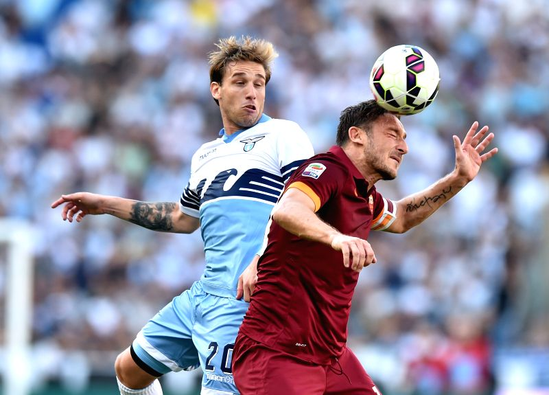 Rome's Francesco Totti (R) vies with Lazio's Senad Lulic during the Italian Serie A soccer match against Lazio at the Olympic Stadium in Rome, Italy, May 25, 2015. Rome ...