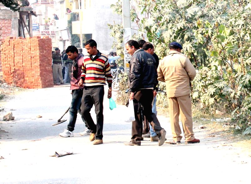 Police personals investigate at the blast site where a 10-year-old boy was killed in an explosion that took place at a garbage dump, near DAV college in Roorkie, Uttarakhand on Dec. 6, 2014.