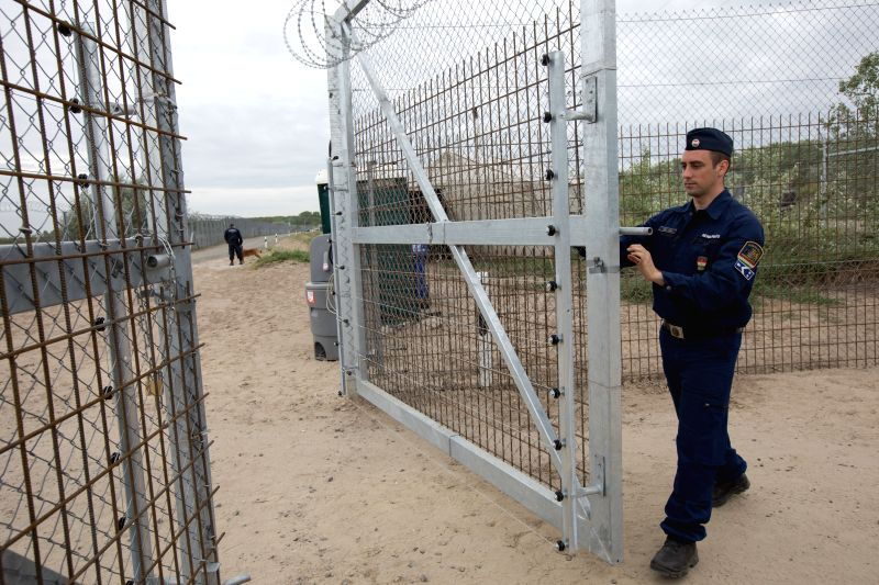 ROSZKE, April 28, 2017 - A Hungarian police closes the gate to the road between the double border fences near Roszke, Hungary, on April 28, 2017. The second line of a double-row fence alongside the ...