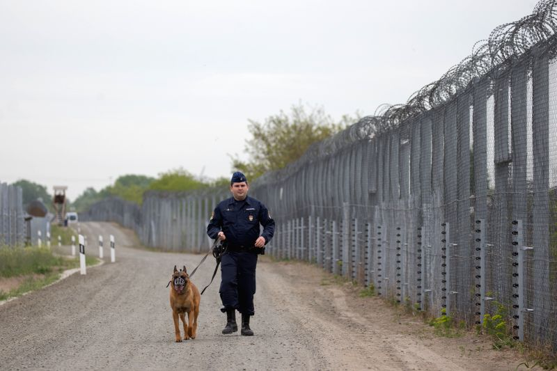 ROSZKE, April 28, 2017 - A Hungarian police officer patrols with his dog on the road between the double border fences near Roszke, Hungary, on April 28, 2017. The second line of a double-row fence ...