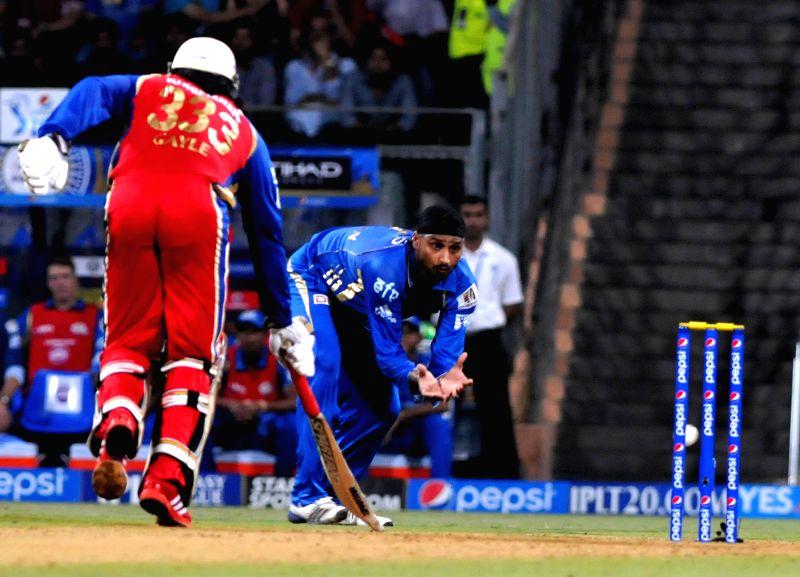 Royal Challengers Bangalore batsman Chris Gayle and Mumbai Indians bowler Harbhajan Singh in action during the 27th match of IPL 2014 between Mumbai Indians and Royal Challengers Bangalore at ... - Chris Gayle and Harbhajan Singh