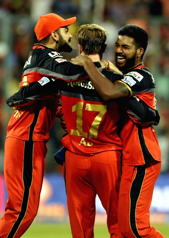 Royal Challengers Bangalore players celebrate fall of a wicket during an IPL match between Royal Challengers Bangalore and Mumbai Indians at M Chinnaswamy Stadium in Bengaluru, on May 11, ...