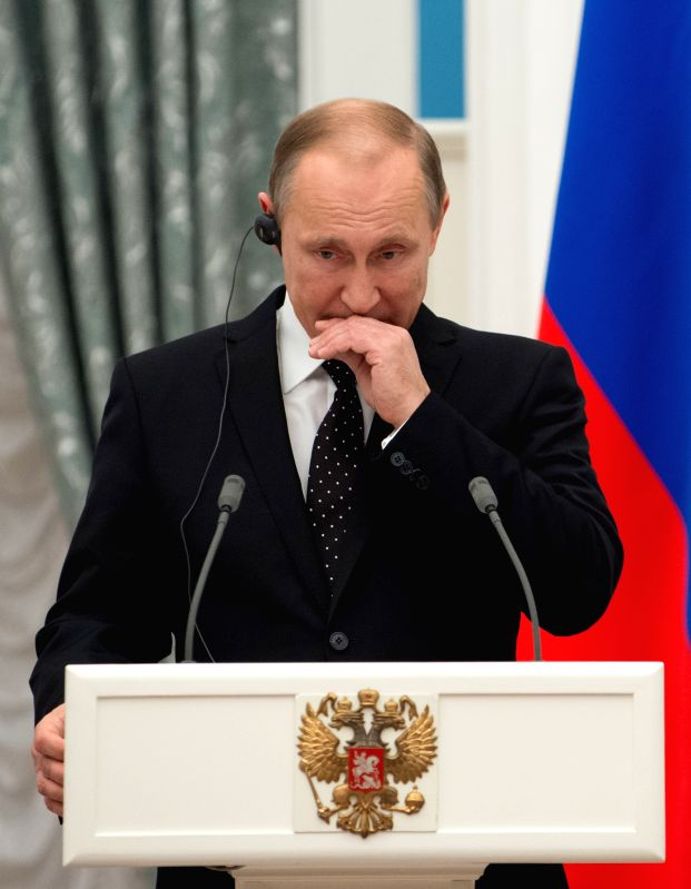 Russian President Vladimir Putin reacts during a joint press conference with his French counterpart Francois Hollande (not in the picture) after their meeting in ...